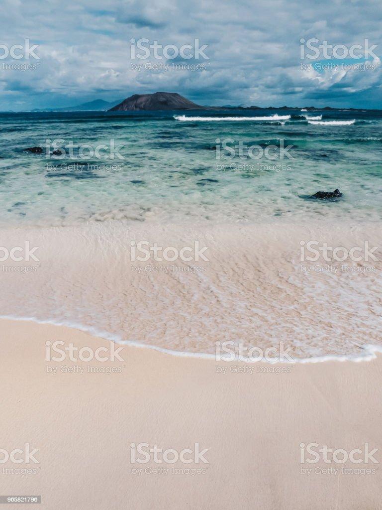 Prachtige turquoise oceaanwater en wit zand in een strand op Fuerteventura, Canarische eilanden. Isla de Lobos en Lanzarote op de achtergrond. - Royalty-free Achtergrond - Thema Stockfoto
