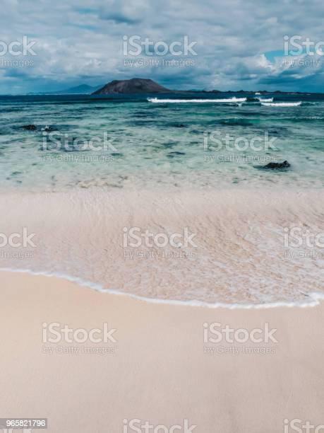 Prachtige Turquoise Oceaanwater En Wit Zand In Een Strand Op Fuerteventura Canarische Eilanden Isla De Lobos En Lanzarote Op De Achtergrond Stockfoto en meer beelden van Achtergrond - Thema