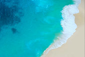 Aerial view of beautiful turquoise sea waves splashing on the shoreline