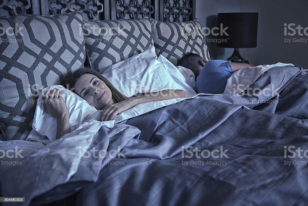 Beautiful twenty something laying in bed blissfully happy stock photo