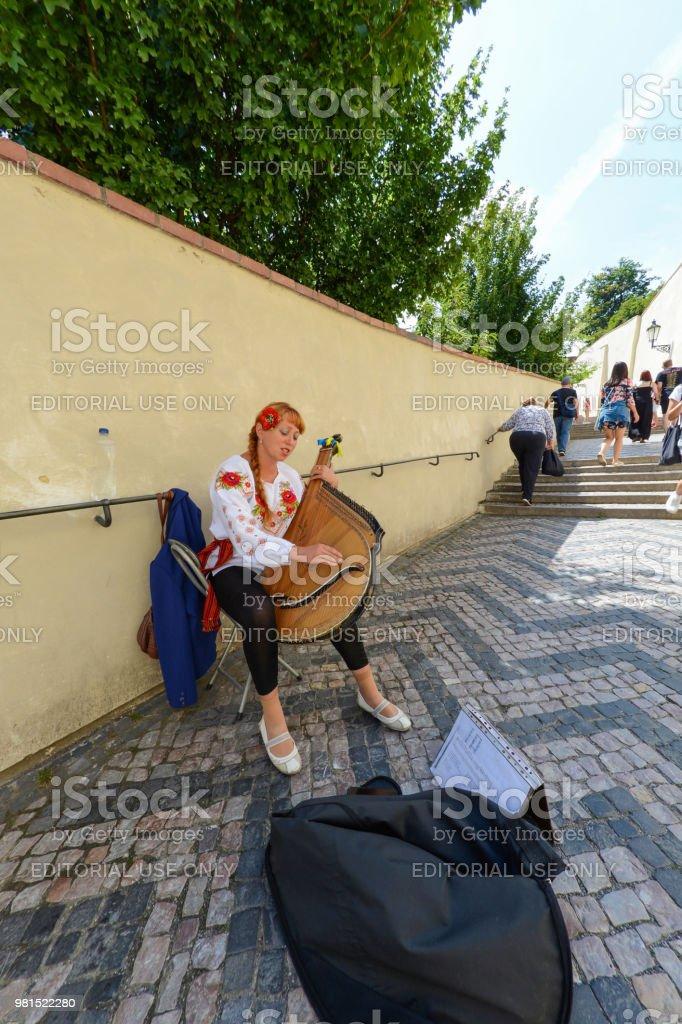 Beautiful Ukrainian woman playing a musical instrument (bandura) on the streets of Prague. стоковое фото