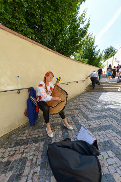 Cтоковое фото Beautiful Ukrainian woman playing a musical instrument (bandura) on the streets of Prague.