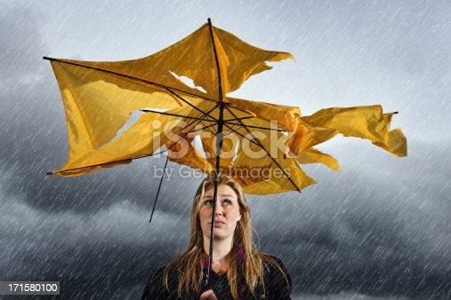 A beautiful young blonde woman sheltering under a torn and tattered yellow umbrella looks up miserably as she waits for a thunderstorm to pass.