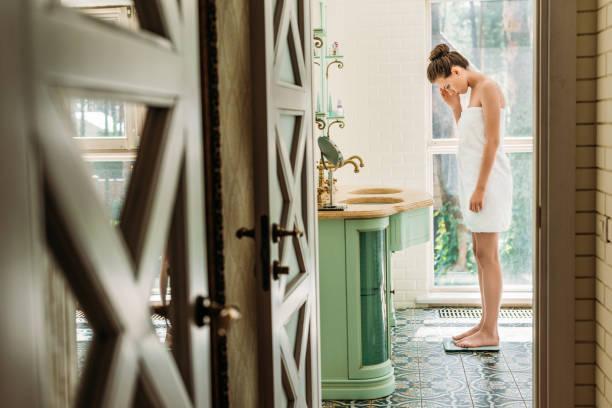 mooie streek vrouw in een handdoek reputatie op digitale weegschaal in badkamer - lichaamsbewustzijn stockfoto's en -beelden