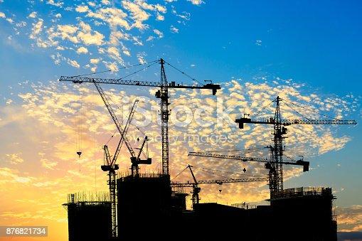 Urban construction site buildings and crane silhouette landscape at sunset
