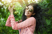Outdoor image of beautiful, happy late teen urban girl holding tree branch full of Asian pear in nature at day time. She is giving toothy smile wearing sunglasses, her long hair are flying in air. One person, horizontal composition with selective focus and copy space.
