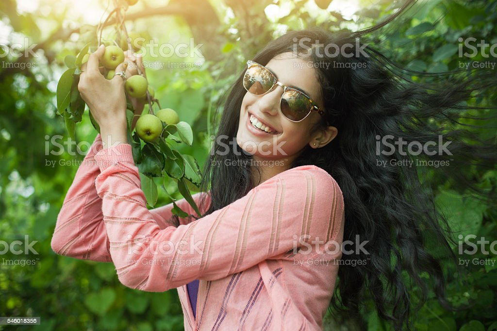 Beautiful urban girl holding tree branch full of Asian pear. stock photo