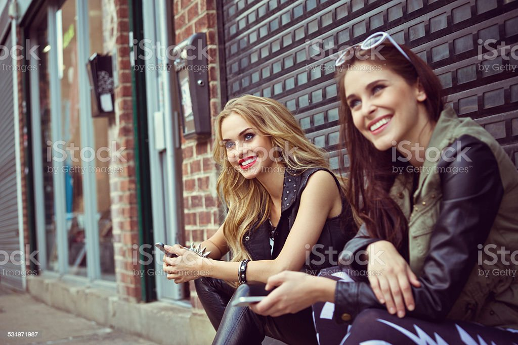 Beautiful urban girls with smart phones Two smiling beautiful young women sitting on the city street and holding smart phones in hands. 20-24 Years Stock Photo