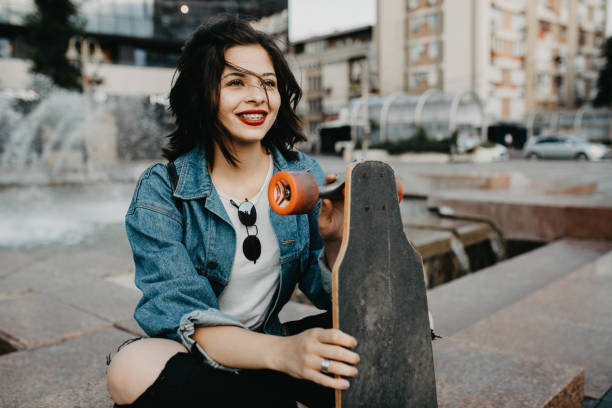 Beautiful Urban young female in the city with her longboard. stock photo