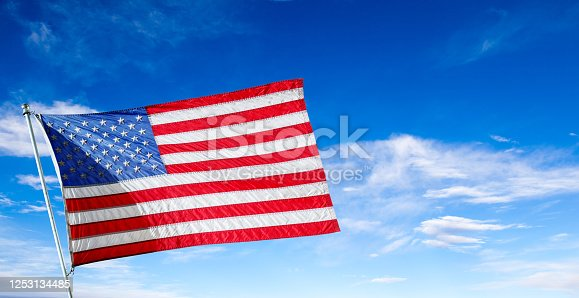 Beautiful flag of the United States of America flying high in the blue sky with copy space. Concept of July 4 Independence Day, Memorial Day or other US celebrations.