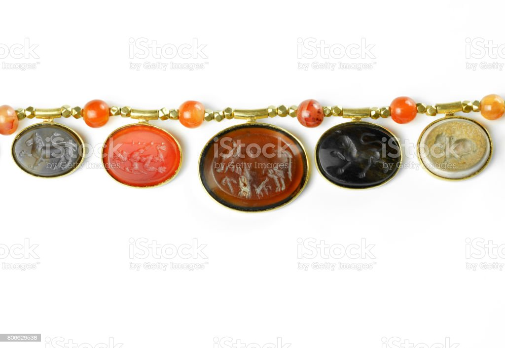 Beautiful varieties of ancient Pyu intaglios mounted in modern gold pendants stringed onto ancient small gold beads separated with round carnelian beads on white background , Myanmar stock photo