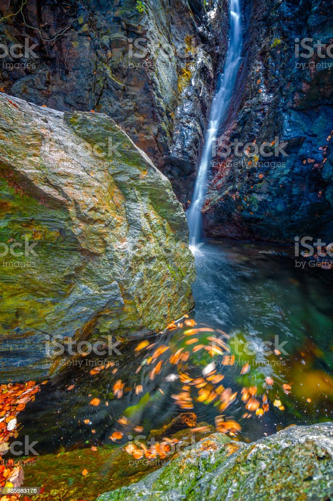 Beautiful veil waterfalls, mossy rocks, rotating leaves stock photo