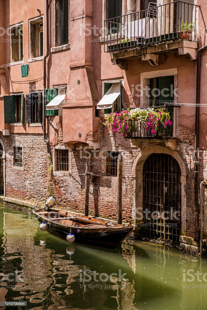 Beautiful Venice canal with boat and balcon with flowers, Summer stock photo