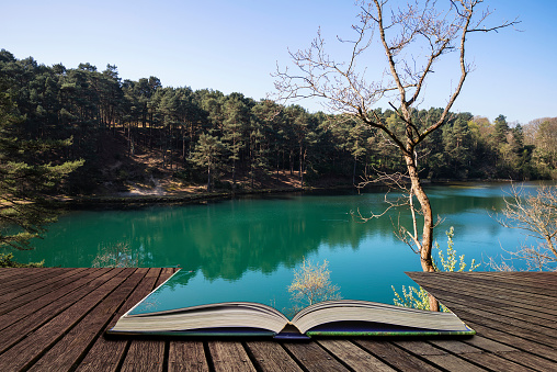 Beautiful vibrant landscape image of old clay pit quarry lake with unusual colored green water concept coming out of pages in open book