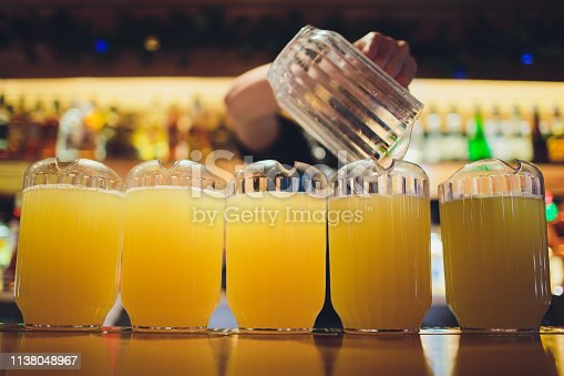 istock Beautiful vibrant picture of gold coloured beer glasses assortment, on wooden table, a summer sunny day, german unfiltered wheat beer. 1138048967