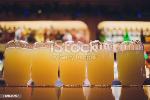 istock Beautiful vibrant picture of gold coloured beer glasses assortment, on wooden table, a summer sunny day, german unfiltered wheat beer. 1138048971