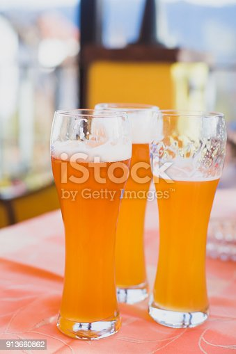 istock Beautiful vibrant picture of gold coloured beer glasses assortment, on wooden table, a summer sunny day, german unfiltered wheat beer 913660862