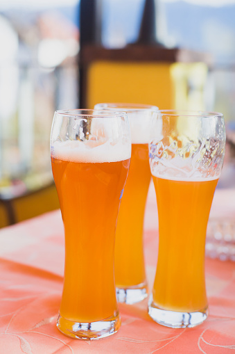 913660988 istock photo Beautiful vibrant picture of gold coloured beer glasses assortment, on wooden table, a summer sunny day, german unfiltered wheat beer 913660862