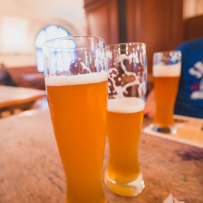 913660988 istock photo Beautiful vibrant picture of gold coloured beer glasses assortment, on wooden table, a summer sunny day, german unfiltered wheat beer 913660870