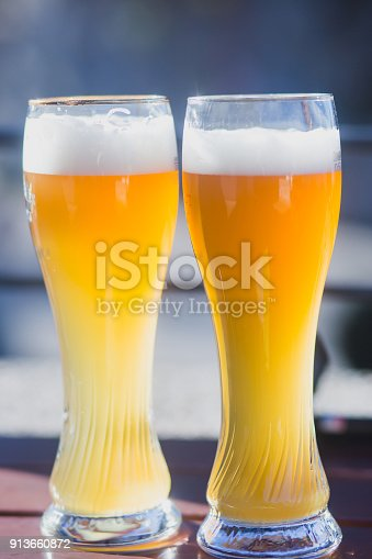 istock Beautiful vibrant picture of gold coloured beer glasses assortment, on wooden table, a summer sunny day, german unfiltered wheat beer 913660872