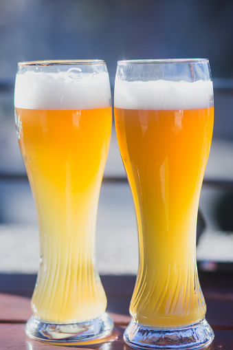 913660988 istock photo Beautiful vibrant picture of gold coloured beer glasses assortment, on wooden table, a summer sunny day, german unfiltered wheat beer 913660872