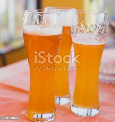 913660896 istock photo Beautiful vibrant picture of gold coloured beer glasses assortment, on wooden table, a summer sunny day, german unfiltered wheat beer 913660874