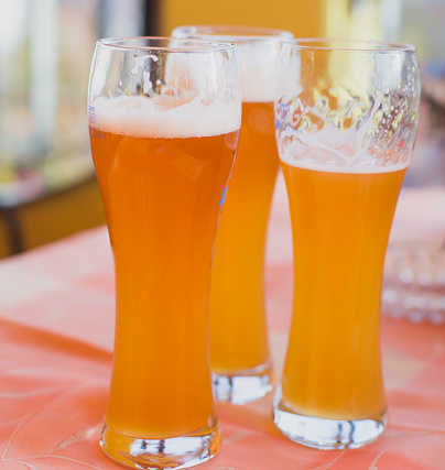 913660988 istock photo Beautiful vibrant picture of gold coloured beer glasses assortment, on wooden table, a summer sunny day, german unfiltered wheat beer 913660874