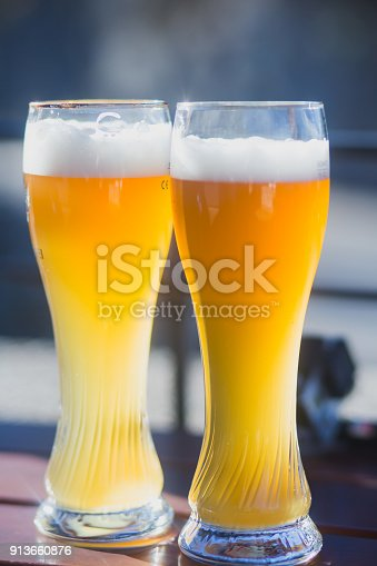istock Beautiful vibrant picture of gold coloured beer glasses assortment, on wooden table, a summer sunny day, german unfiltered wheat beer 913660876