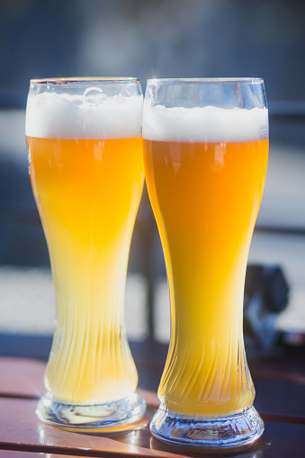 913660988 istock photo Beautiful vibrant picture of gold coloured beer glasses assortment, on wooden table, a summer sunny day, german unfiltered wheat beer 913660892