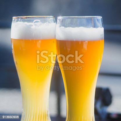 istock Beautiful vibrant picture of gold coloured beer glasses assortment, on wooden table, a summer sunny day, german unfiltered wheat beer 913660908