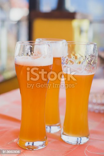 istock Beautiful vibrant picture of gold coloured beer glasses assortment, on wooden table, a summer sunny day, german unfiltered wheat beer 913660936