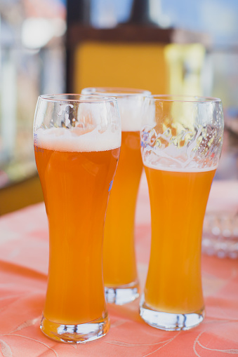 913660988 istock photo Beautiful vibrant picture of gold coloured beer glasses assortment, on wooden table, a summer sunny day, german unfiltered wheat beer 913660936