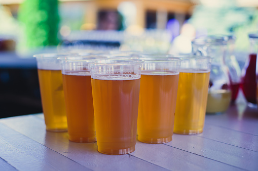 913660988 istock photo Beautiful vibrant picture of gold coloured beer glasses assortment, on wooden table, a summer sunny day, german unfiltered wheat beer 913660944