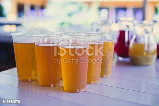 913660896 istock photo Beautiful vibrant picture of gold coloured beer glasses assortment, on wooden table, a summer sunny day, german unfiltered wheat beer 913660978