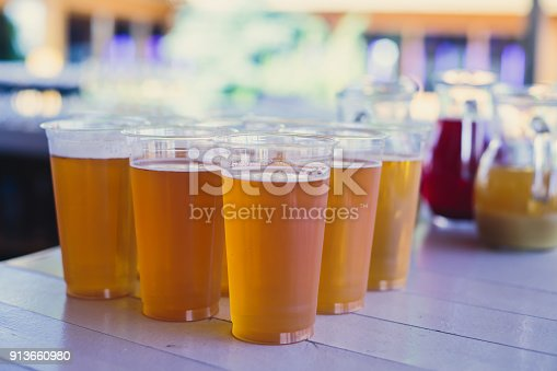 istock Beautiful vibrant picture of gold coloured beer glasses assortment, on wooden table, a summer sunny day, german unfiltered wheat beer 913660980