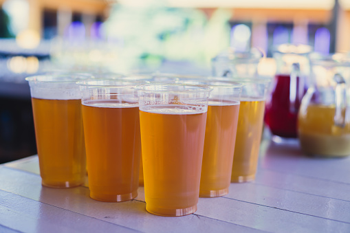 913660988 istock photo Beautiful vibrant picture of gold coloured beer glasses assortment, on wooden table, a summer sunny day, german unfiltered wheat beer 913660980
