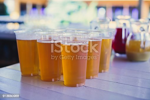 istock Beautiful vibrant picture of gold coloured beer glasses assortment, on wooden table, a summer sunny day, german unfiltered wheat beer 913660988
