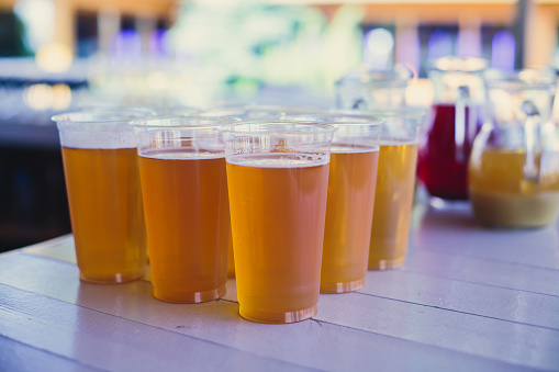 913660988 istock photo Beautiful vibrant picture of gold coloured beer glasses assortment, on wooden table, a summer sunny day, german unfiltered wheat beer 913660988
