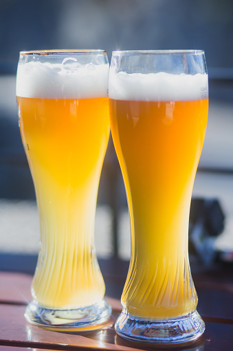913660988 istock photo Beautiful vibrant picture of gold coloured beer glasses assortment, on wooden table, a summer sunny day, german unfiltered wheat beer 913660994