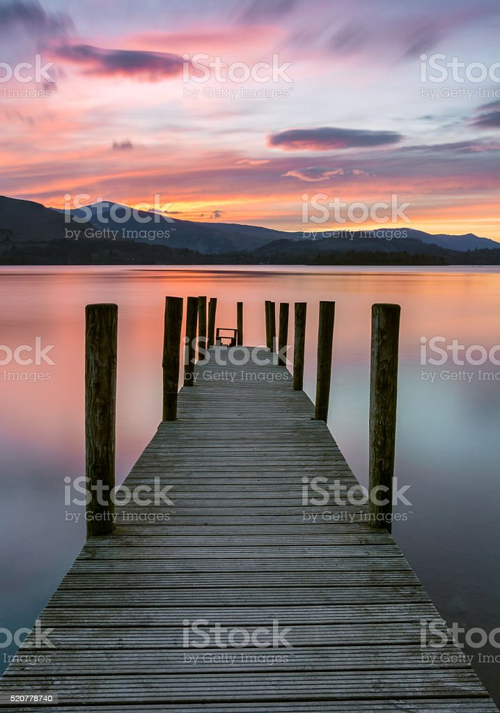 Beautiful Vibrant Pink And Purple Sunset With Wooden Jetty. stock photo
