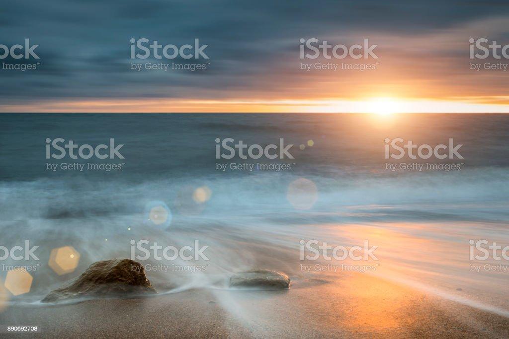 Beautiful vibrant sunset landscape image of Burton Bradstock golden cliffs in Dorest England stock photo