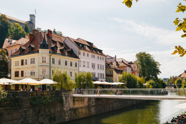 A beautiful view at river Ljubljanica, Cankarjevo Nabrezje, bridges and Ljubljana Castle tower, the tourist centre of Ljubljana, the capital of Slovenia. With people relaxing in cafes at the both banks of the river Ljubljana, Slovenia - September, 8 2018: A beautiful view at river Ljubljanica, Cankarjevo Nabrezje, bridges and Ljubljana Castle tower, the tourist centre of Ljubljana, the capital of Slovenia. With people relaxing in cafes at the both banks of the river ljubljana castle stock pictures, royalty-free photos & images