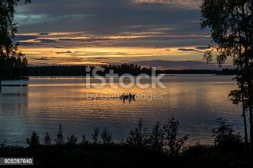 Evening view of people fishing in a small fishing boat on a lake in sunset light with beautiful reflections of orange and pink light in the water