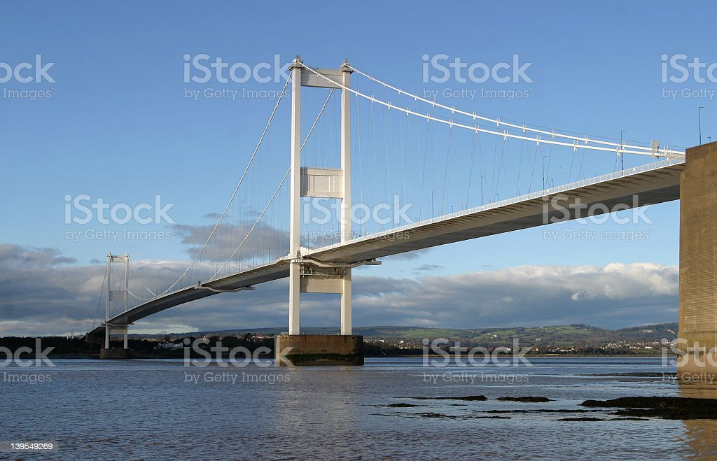 A beautiful view of a suspension bridge over the water stock photo