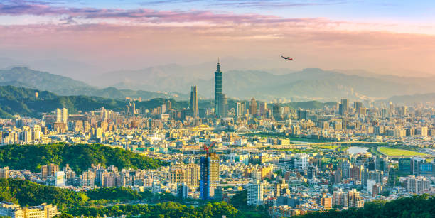Beautiful view of an airplane flying over Taipei city at sunset stock photo