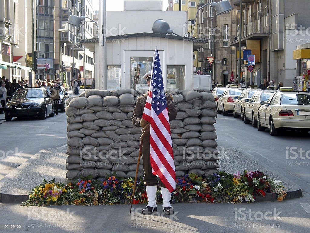 Beautiful view of checkpoint Charlie holding a US flag royalty-free stock photo