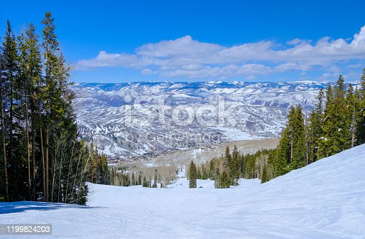 Beautiful view of slope of Aspen-Snowmass, Colorado, ski resort on nice winter day; small buildings of village buildings appear at the bottom of the slope; mountain range and blue sky in background