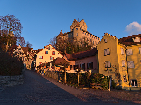 Meersburg, Germany - 12-26-2020: Beautiful view of historic center with empty cobblestone street, old buildings and landmark Meersburg castle on the slope in evening light in winter season.