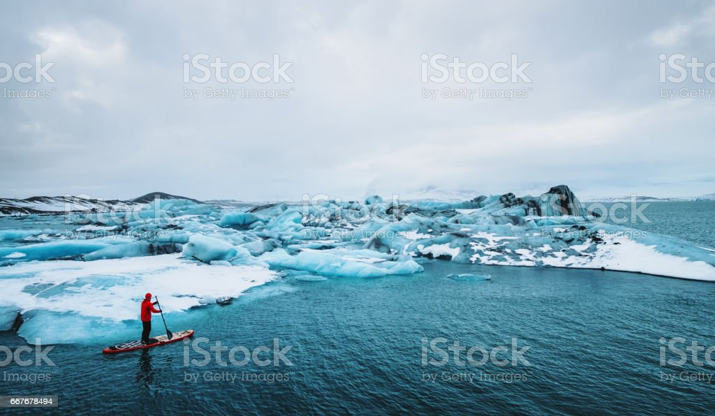 Beautiful view of icebergs glacier lagoon with a guy paddle boarding (sup), global warming and climate change concept – zdjęcie