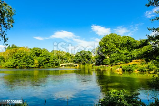 Beautiful view of lake in Central Park in New York City, New York on clear day; bridge in background; sky reflects in water